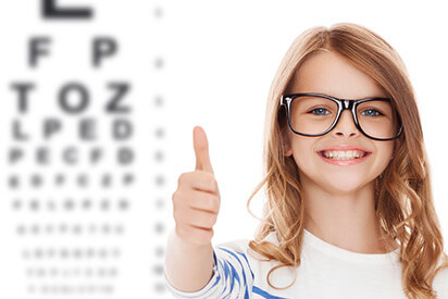 Mädchen mit Kinderbrille vor Lesetafel