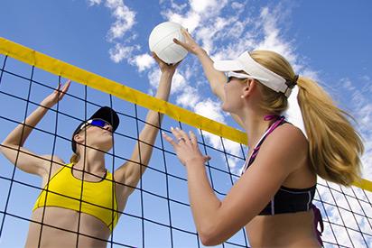 Zwei                 Sportlerinnen spielen Beachvolleyball mit Beachvolleyball Brillen