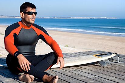 Surfer sitzt mit                 Surfboard und Wassersportbrille am Strand